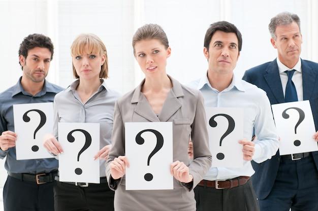 Geschäftsgruppe von personen, die fragezeichen mit nachdenklichem ausdruck im büro halten