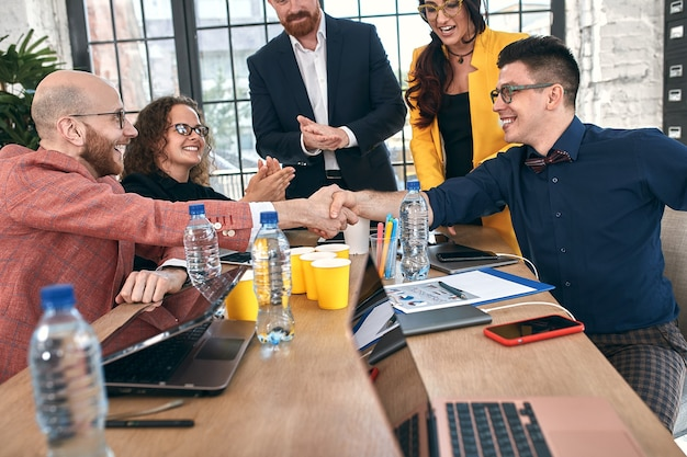Geschäftshändedruck bei treffen oder verhandlungen im büro. partner sind zufrieden, weil sie vertrags- oder finanzpapiere unterzeichnen. selektiver fokus.