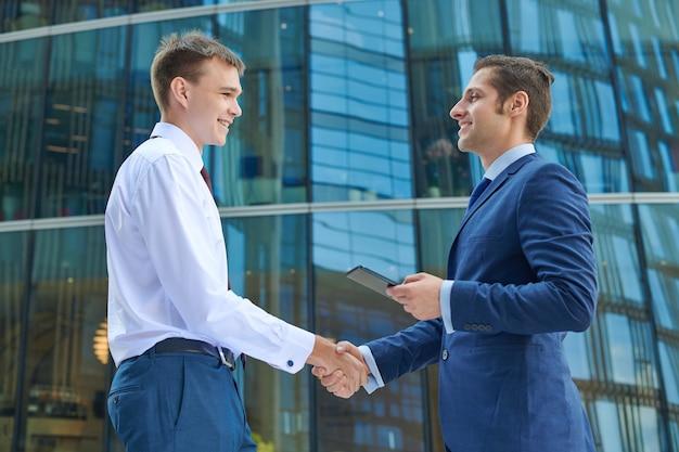 Geschäftshändedruck im freien auf bürozentrumhintergrund. konzept für partnerschaftstreffen. erfolgreiche geschäftsleute, die nach gutem geschäft händeschütteln.