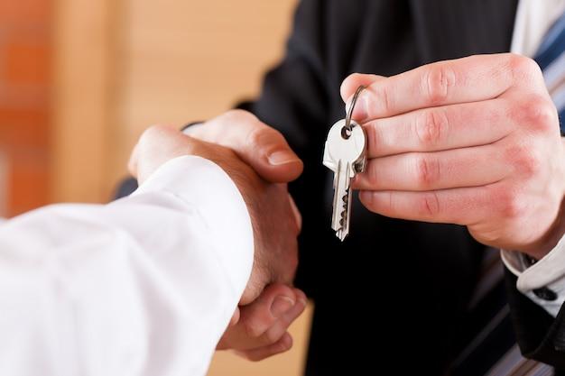Geschäftshändedruck mit dem geben von schlüsseln