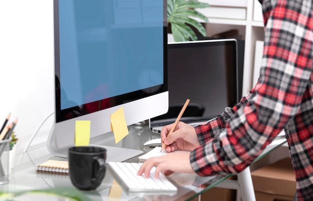 Geschäftshand, die auf computertastatur für das suchen von informationen über den bürodesktop schreibt.