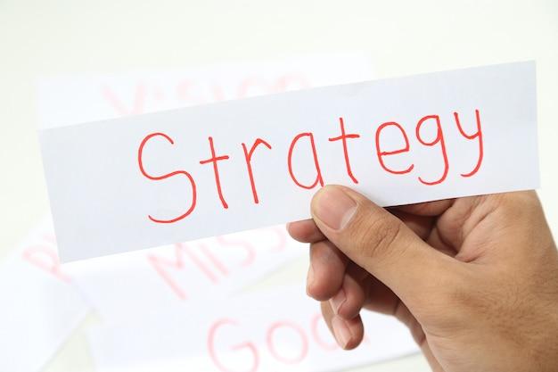 Geschäftshand, die ein stück strategiepapier schreibt