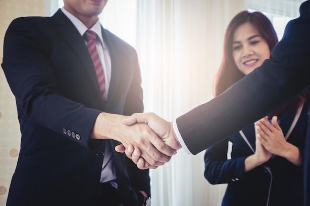 Geschäftshanderschütterungs-geschäftserfolg mit der klatschenden frau