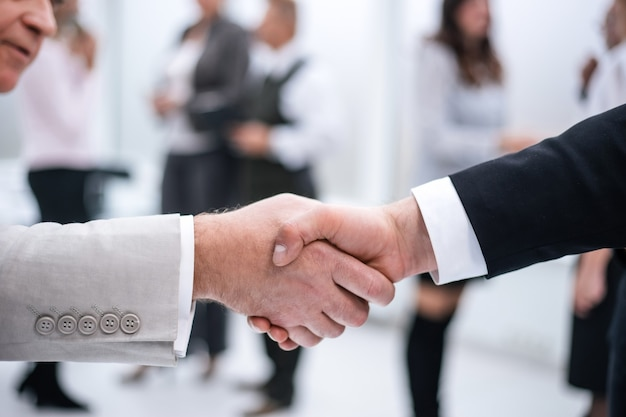 Geschäftshandschlag auf bürohintergrund