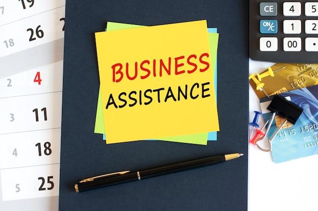 Geschäftshilfe-text auf gelber papierquadratform. notepad rechner kreditkarten stift briefpapier auf dem desktop geschäfts- und bildungskonzept selektiver fokus