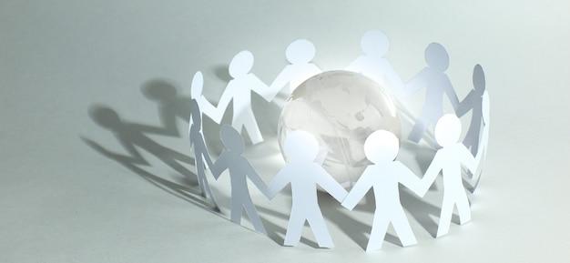 Geschäftshintergrund.teampapiermänner, die um die glaskugel herumstehen.foto mit kopienraum