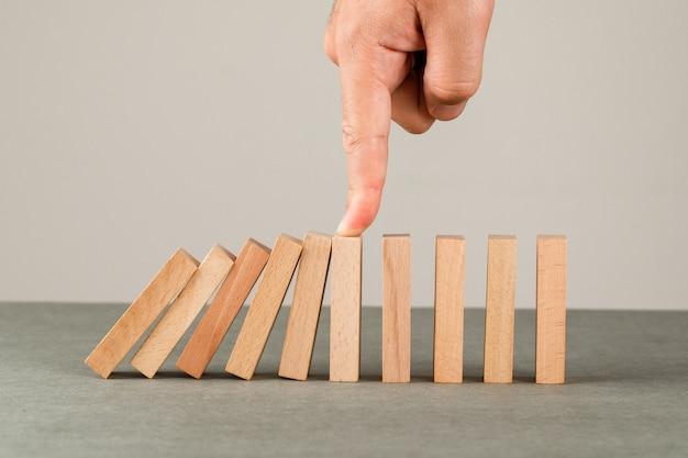 Geschäftsideenkonzept auf grauer und weißer wandseitenansicht. hand stoppt den dominoeffekt.