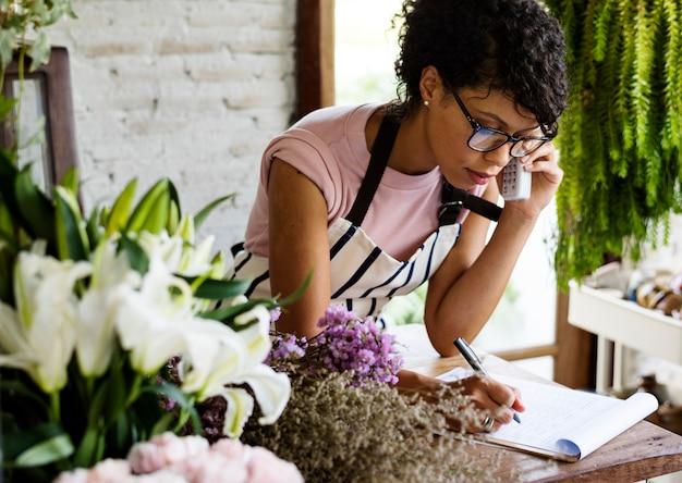 Geschäftsinhaber, der am telefon spricht und kenntnis nimmt