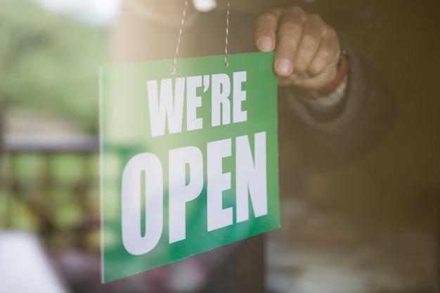 Geschäftsinhaber, der ein offenes schild an einer glastür hängt. wir sind offen.