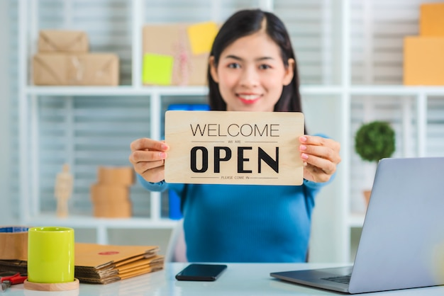 Geschäftsinhaber der jungen asiatischen frau, die offenes zeichen hält