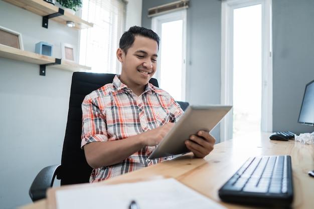 Geschäftsinhaber, der mit tablette in seinem büro entspannt