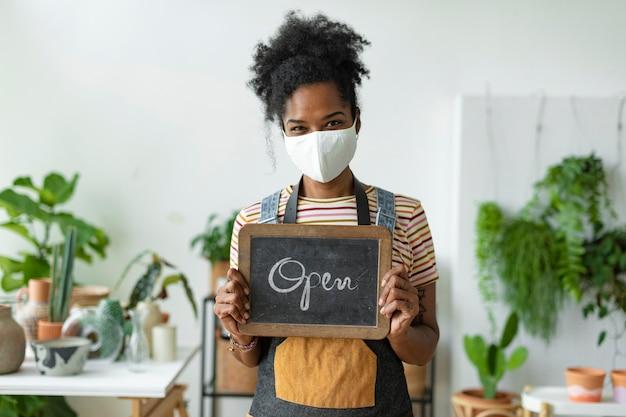Geschäftsinhaber mit offenem schild in der neuen normalität