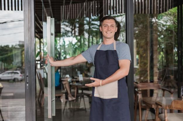 Geschäftsinhaber öffnet die tür für den kunden zu kommen