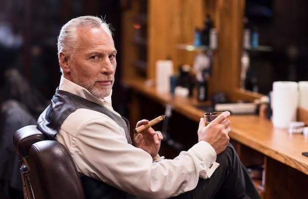Geschäftsinhaber. seitenansichtporträt des hübschen älteren mannes, der vorwärts schaut, während auf sessel mit cognacglas und zigarre sitzend.