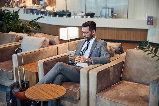 Geschäftsinhaber sitzt mit whisky und telefon