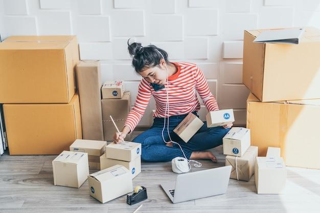 Geschäftsinhaberin der asiatischen frauen, die zu hause mit packbox am arbeitsplatz arbeitet