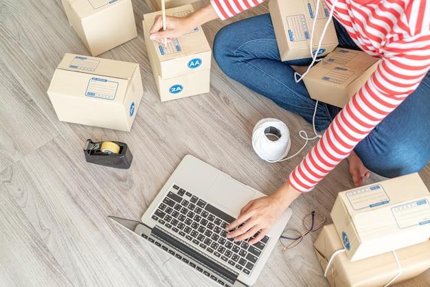 Geschäftsinhaberin der asiatischen frauen, die zu hause mit packbox am arbeitsplatz, kmu-unternehmer des online-einkaufs oder online-verkaufskonzept arbeitet