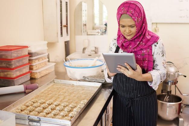 Geschäftsinhaberin der muslimischen frau, die ihr gebäck prüft