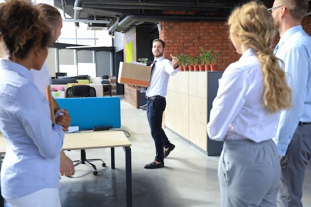 Geschäftskollegen begleiten den entlassenen mitarbeiter aus dem büro und zeigen fick.