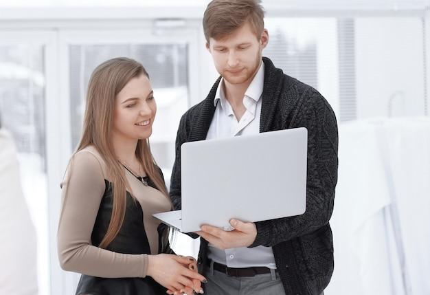 Geschäftskollegen benutzen einen laptop, der im büro steht