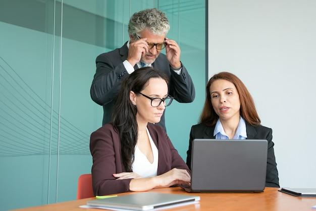 Geschäftskollegen, die die projektpräsentation auf dem computer beobachten und die anzeige des offenen laptops betrachten
