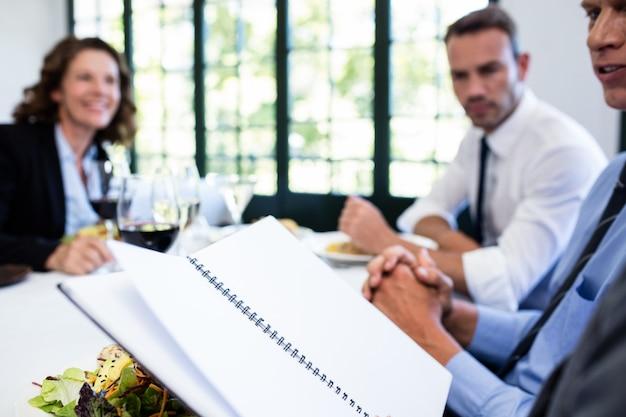 Geschäftskollegen, die eine datei betrachten und sich besprechen