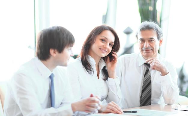 Geschäftskollegen, die finanzstatistiken analysieren, die an einem schreibtisch im büro sitzen.