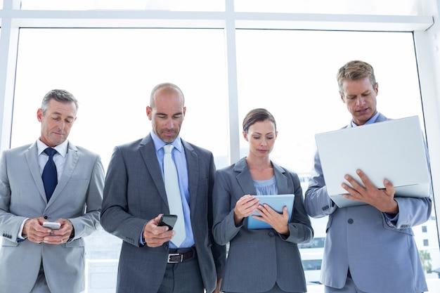 Geschäftskollegen, die ihre multimediageräte verwenden