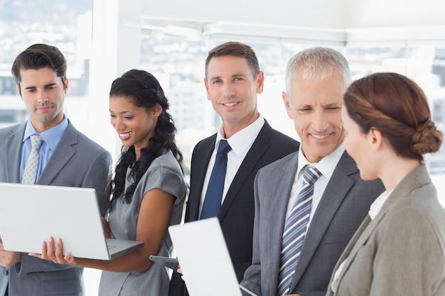 Geschäftskollegen, die ihre multimediageräte zueinander zeigen