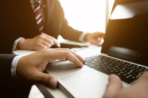 Geschäftskollegen, die jährliche verkaufsleistung abschließen und berichte über laptop am arbeitsplatz analysieren