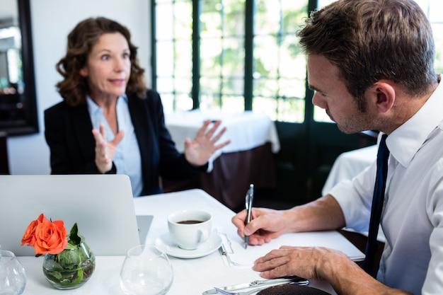 Geschäftskollegen, die kenntnisse beim haben einer sitzung besprechen und nehmen
