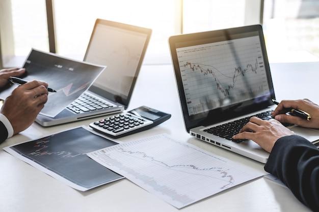 Geschäftskollegen, die mit computer arbeiten, börse besprechen und analysieren