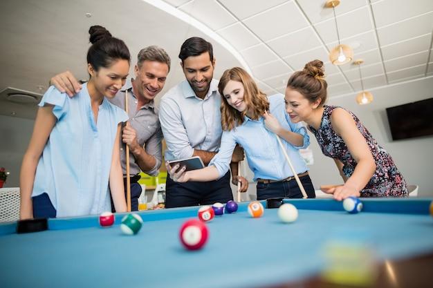Geschäftskollegen, die mobiltelefon beim billardspielen in büroräumen verwenden