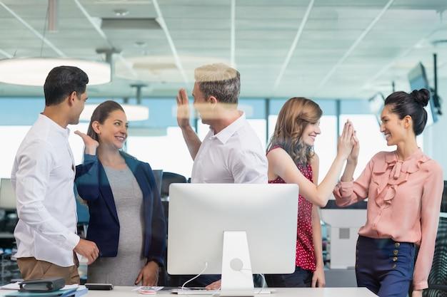 Geschäftskollegen geben high five während des meetings am schreibtisch im büro