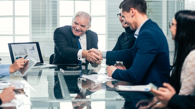 Geschäftskollegen händeschütteln während eines arbeitstreffens. das konzept der teamarbeit