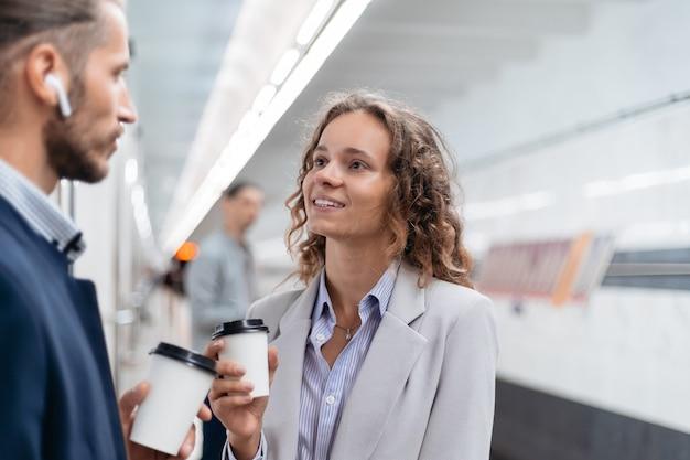 Geschäftskollegen mit kaffee zum mitnehmen stehen auf dem u-bahnsteig