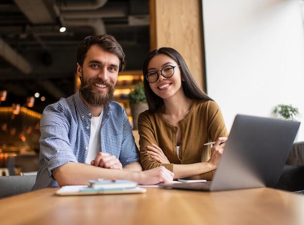 Geschäftskollegen sitzen am tisch im büro, verwenden einen laptop und arbeiten für ein startprojekt zusammen. erfolgreiches geschäfts- und karrierekonzept. porträt junger glücklicher entwickler am arbeitsplatz