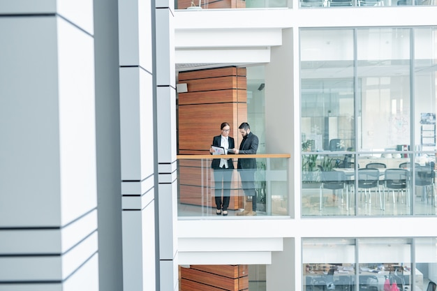 Geschäftskollegen stehen im korridor des bürozentrums und diskutieren daten mit papieren und geräten