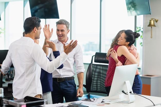 Geschäftskollegen umarmen und feiern im büro