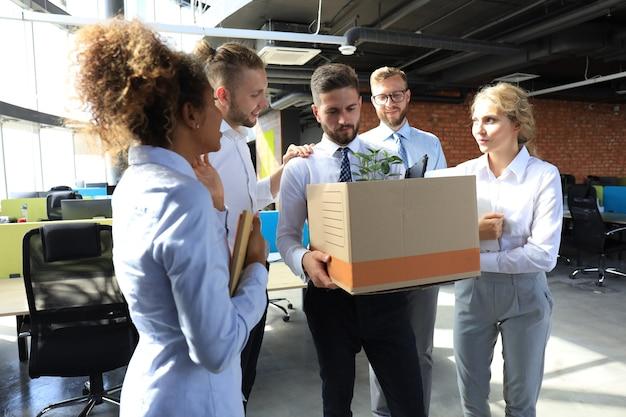 Geschäftskollegen verabschieden sich vom entlassenen mitarbeiter.