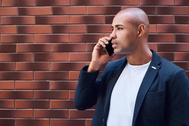 Geschäftskommunikation junger mann, der an der wand steht und auf smartphone nachdenkliche seitenansicht spricht