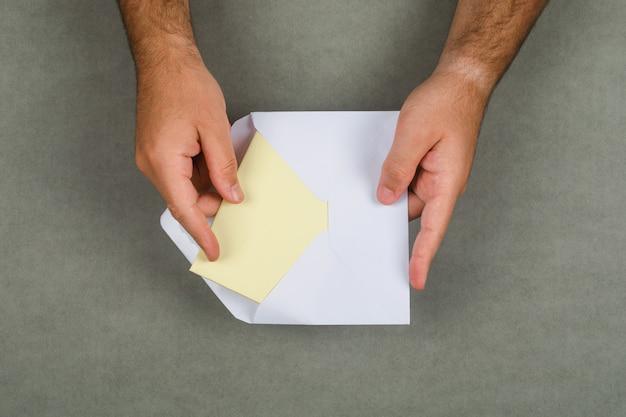 Geschäftskonzept auf grauer oberfläche flach legen. mann, der brief aus umschlag nimmt.