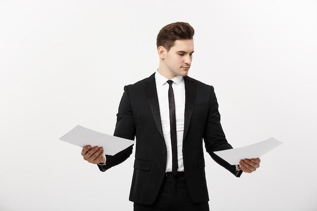 Geschäftskonzept: aufmerksamer gutaussehender geschäftsmann, der papierbericht vergleicht. getrennt über weißem grauem hintergrund.