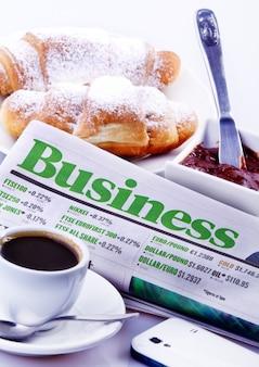 Geschäftskonzept aus zeitung, croissants, marmelade, schönem kaffee und smartphone.