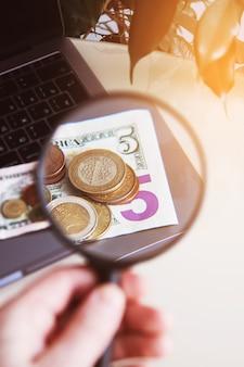 Geschäftskonzept, banknoten und münzen werden unter einer lupe betrachtet.