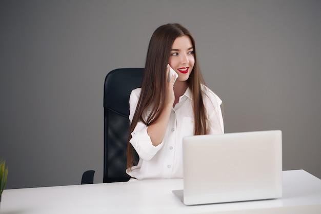 Geschäftskonzept - brünette geschäftsfrau, die im büro am telefon spricht,