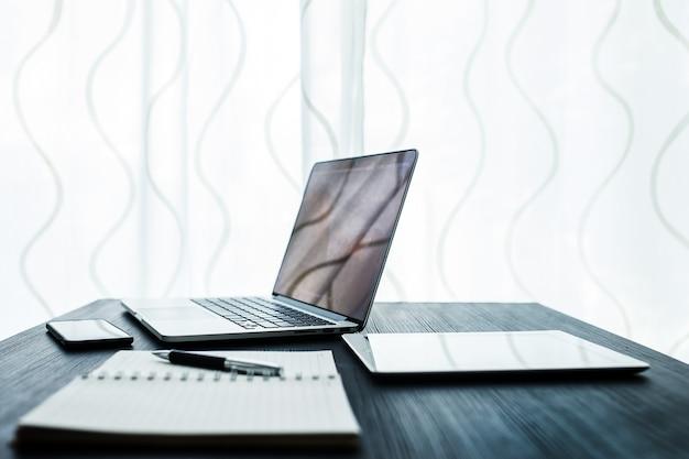 Geschäftskonzept, büroarbeitsplatz mit laptop auf hölzerner tabelle gegen die fenster
