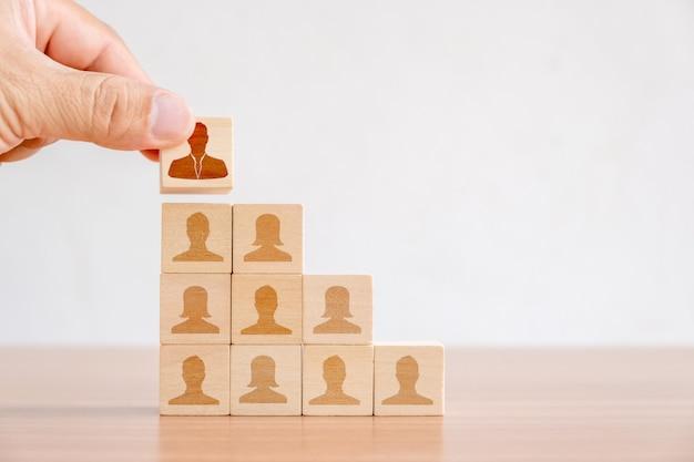 Geschäftskonzept des personal- und talentmanagements und der einstellung. hand von männern, die hölzernen würfelblock auf spitzentreppenhaus setzen