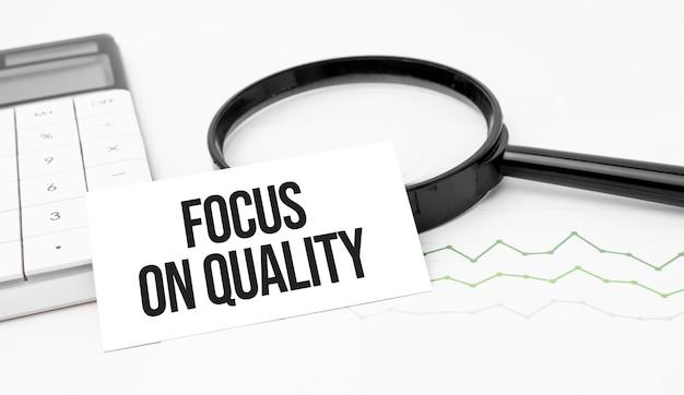 Geschäftskonzept. draufsicht auf taschenrechner, lupe, stift, tischuhr und notizbuch geschrieben fokus auf qualität auf holzhintergrund.