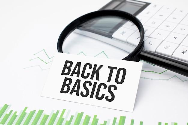 Geschäftskonzept. draufsicht auf taschenrechner, lupe, stift, tischuhr und notizbuch zurück zu grundlagen auf holzhintergrund geschrieben.